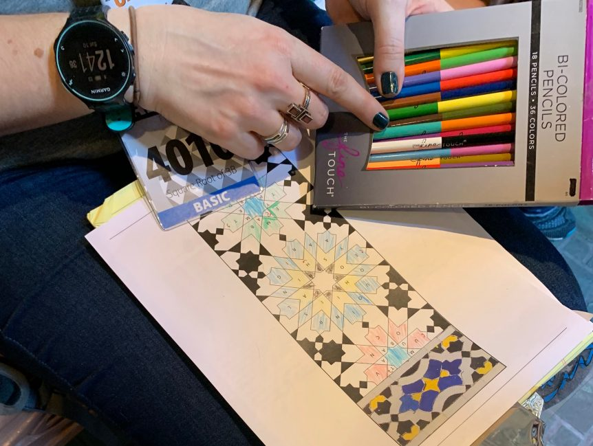 A woman holds a pack of colored pencils in her hand and a colored image on her lap